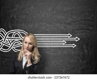 Young businesswoman thinking and drawing arrowa symbol on wall