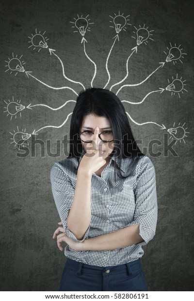 Young businesswoman thinking with many arrows and bulbs above her head