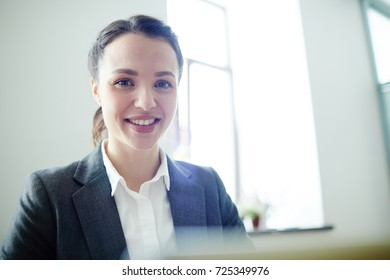 Young businesswoman with toothy smile looking at camera in office