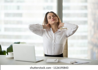 Young businesswoman touching massaging stiff neck after sedentary computer work in incorrect posture, fatigued employee taking work break for doing easy office exercises to relieve pain in muscles