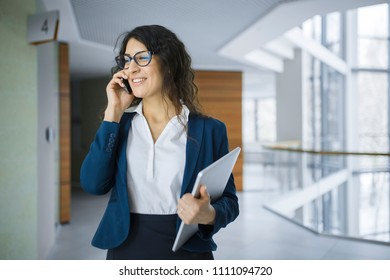 Young businesswoman with touchpad talking on cellphone