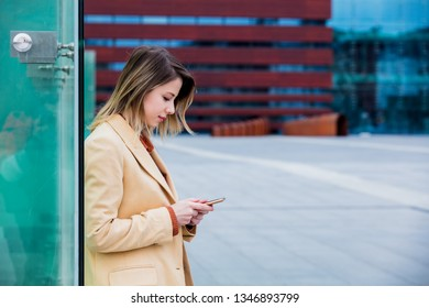 Young businesswoman typing message by phone on the city square with modern building at outdoor