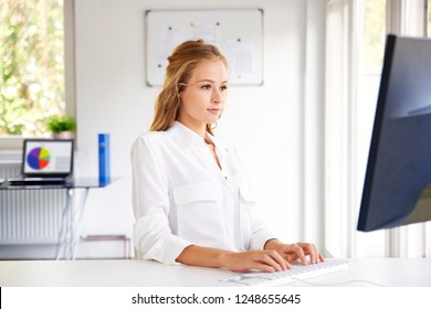 Young businesswoman typing on computer's keyboard while sitting at office desk and working on new project.