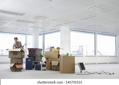 Young businesswoman unpacking cartons in an empty office space