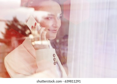 Young businesswoman using cell phone in office