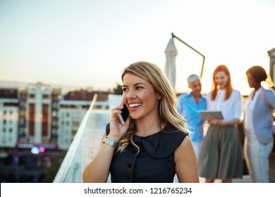 Young businesswoman using cellphone during meeting
