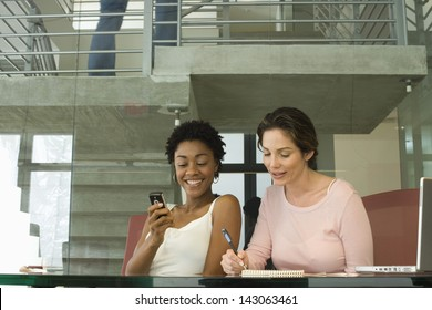 Young businesswoman using cellphone with female colleague noting down on notepad in office
