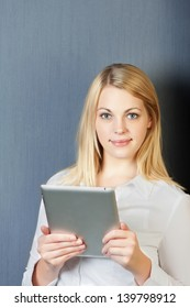 Young businesswoman using digital tablet isolated over blue background