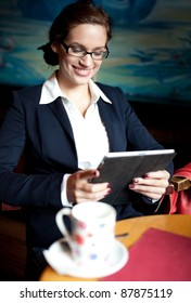 Young businesswoman using her tablet computer on a coffee break. Selective focus