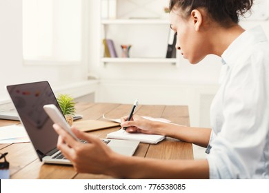 Young businesswoman using laptop with blank screen, while holding smartphone and writing notes, copy space