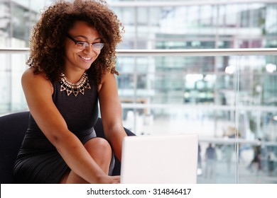 Young businesswoman using laptop computer in modern interior