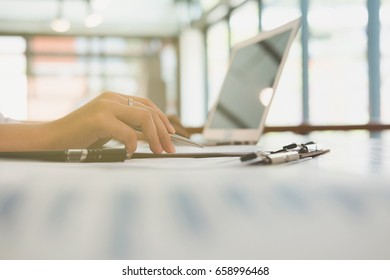 young businesswoman using laptop computer at workplace.  young female entrepreneur woman working with business document at office. Marketing plan researching. Paperwork on table.