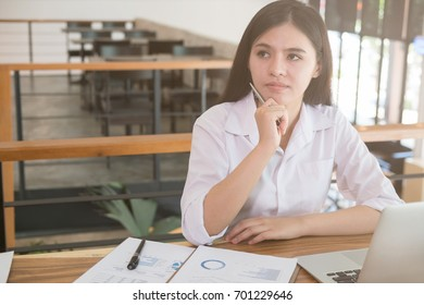 young businesswoman using laptop computer at workplace.  young female entrepreneur woman working with business document analyze graph and chart at office. Marketing plan researching. Paperwork