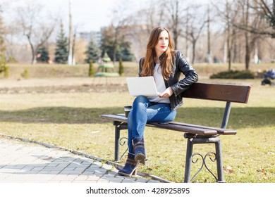 Young businesswoman using laptop sitting on bench in the park. European smiling student girl with notebook reading or learning in the park