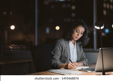 Young businesswoman using a laptop and writing notes while working overtime at her office desk late in the evening