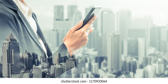 Young businesswoman using mobile phone with modern city buildings background. Future telecommunication technology and internet of things ( IOT ) concept.