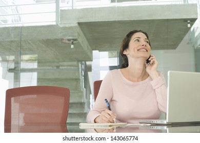 Young businesswoman using mobile phone while writing on notepad with laptop on table