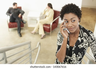 Young businesswoman using mobile phone on stairway with colleagues in background