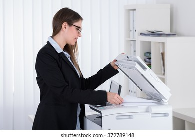 Young Businesswoman Using Printer Machine In Office