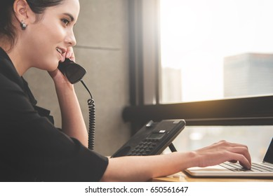 Young Businesswoman using telephone and laptop computer at her workplace. Call center, Customer service. Beautiful Woman talking with client.