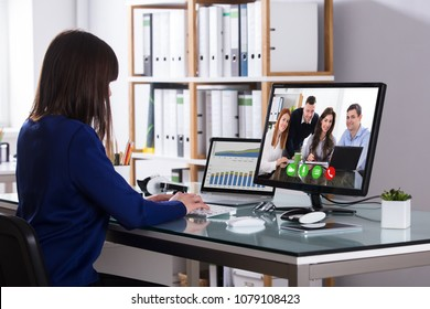 Young Businesswoman Video Conferencing With Colleagues On Computer At Workplace