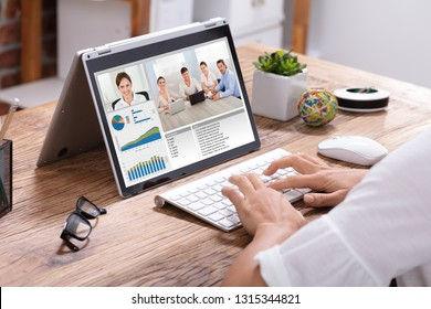 Young Businesswoman Video Conferencing With His Colleagues On Laptop Over Wooden Desk In The Office