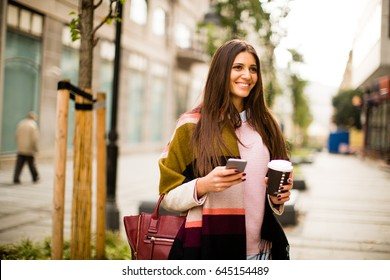 Young businesswoman walking down the street with coffee and cell phone in hand
