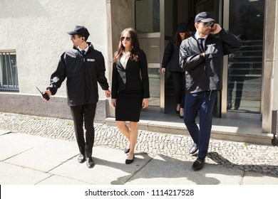 Young Businesswoman Walking On Sidewalk With Her Bodyguards