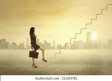 Young businesswoman walking up on stairs for success