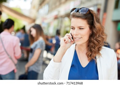 Young businesswoman walking on street, talking on mobilephone.