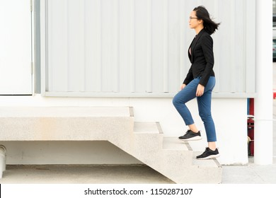 Young businesswoman walking up the stairs with success, copy space.