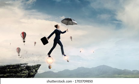 Young businesswoman walking with umbrella