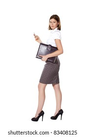 Young businesswoman walking and using phone and holding a leather folder