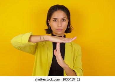 Young businesswoman wearing casual turtleneck sweater and jacket being upset showing a timeout gesture, needs stop, asks time for rest after hard work, demonstrates break hand sign