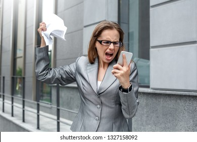 Young businesswoman wearing eyeglasses standing on the city street shouting at busines partner on smartphone angry crumpling the contract