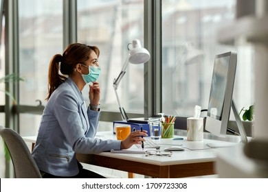 Young businesswoman wearing face mask while working on a computer in the office.