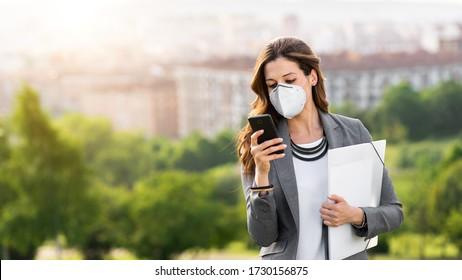 Junge Geschäftsfrau trägt eine Gesichtsmaske im Freien während der Krise des Coronavirus im Covid-19. Professionelle Frau, die ihr Smartphone benutzt.