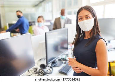 Young businesswoman wearing face mask as protection against Covid-19 and corona virus in open plan office