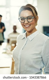 Young businesswoman wearing glasses and smiling while standing in an office with colleagues working behind her