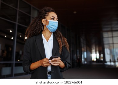 Young businesswoman wearing a medical mask stands near the office center. Officially looking girl with a phone in her hands waiting outside. Leading business during Covid-19 pandemic concept.