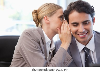 Young businesswoman whispering something to her colleague in a meeting room
