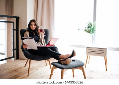 Young businesswoman work at home. Busy woman looking on papers in hand and study. Hold glass of red wine. Laptop on legs. Director of company or CEO.