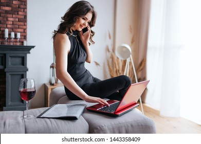 Young businesswoman work at home. Cheerfu lattractive model sit on edge of table and talk on phone. Typing on laptop's keyboard. Glass of red wine stand on table.