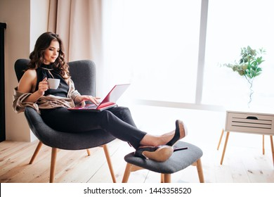 Young businesswoman work at home. Drinking coffe and studying. Holding feet on small stool. Typing on keyboard laptop. Concentrated busy model. Alone in room.