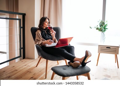 Young businesswoman work at home. Drinking red wine from glass and look to right. Hold phone in hands. Journal and laptop on legs. Remote work. Alone in room. Relaxing.