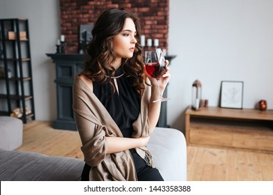 Young businesswoman work at home. Thoughtful calm model hold glass of red wine and look forward. Wear dark dress and brown sweater. Alone in room.