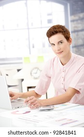 Young businesswoman at work, using laptop computer, holding pen, looking at camera.?