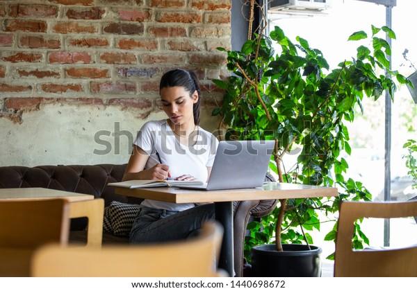 Young businesswoman is working in a cafeteria in her break.Woman taking a break. Enjoying work from coffee shop. Doing Business From coffee shop.