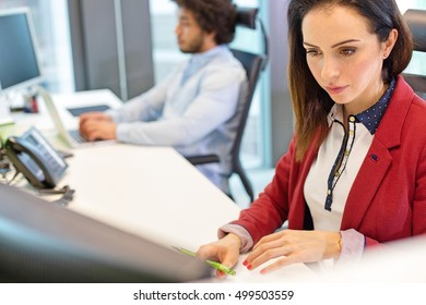 Young businesswoman working at desk with male colleague in background