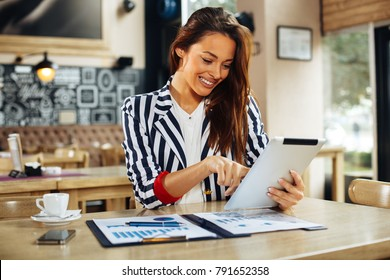 Young businesswoman working with digital tablet in cafe